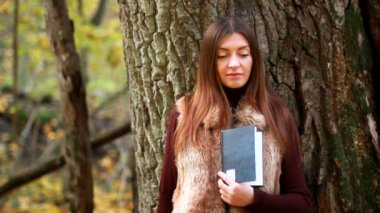 Beautiful girl with book in the autumn park — Stock Video