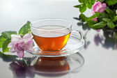 Transparent cup with green tea and fresh herbal bouquet — Stock Photo