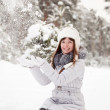 Young woman throwing snow - Stock Photo