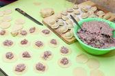 Rolling pin, dough and raw pelmeni — Stock Photo