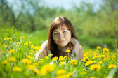 Girl relaxing in dandelion meadow — Stock Photo