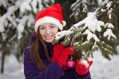 Woman in christmas hat decorates spruce — Stock Photo