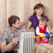 Parents and child  near warm radiator - Stock Photo