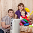 Stock Photo: Parents and child near warm radiator