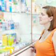 Woman chooses drugs at pharmacy — Stock Photo #13664357