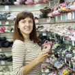 Woman chooses baby shoes - Photo