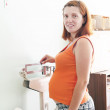 Pregnant woman weighing on scales — Stock Photo