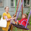Pregnant womwith child on swing — стоковое фото #13665318