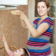Stock Photo: Pregnant womwarms up food