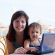 Happy mother and  toddler   with laptop at  beach — Stock Photo