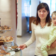 Mother with child takes  pastry  in buffet   — Stock Photo