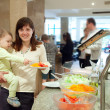 Woman with chid chooses vegetables in buffet — Stock Photo