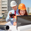 Stock Photo: Two architects works in front of building site