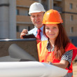 Stock Photo: Two builders works on the building site