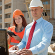Two builders works on the building site — Stock Photo #13665497