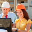 Two architects in front of building site — Stock Photo #13665511
