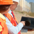 Architects in front of building site — Stock Photo #13665544