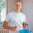 Man with paint roller - Stock fotografie