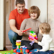 Happy parents and child plays with meccano — Stock Photo #13667185