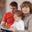 Parents with child looks book — Stock Photo #13667193