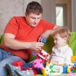 Foto Stock: Father and three-year child plays in home interior