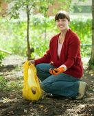 Woman fertilizes the soil — Stock Photo
