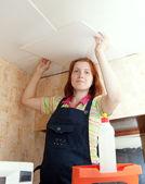 Woman glues ceiling tile — Stock Photo