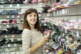 Vrouw kiest baby schoenen — Stockfoto
