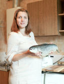 Woman with salmon in the kitchen — Stock Photo