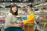 Mãe com criança escolhe sapatos de bebê — Foto Stock