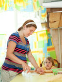 Pregnant woman with child making dumplings — Stock Photo