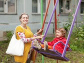 Pregnant woman with child on swing — Stock Photo
