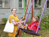 Donna incinta con il bambino sull'altalena — Foto Stock