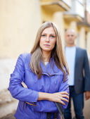 Man walks behind woman on street — Stock Photo