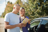 Tourist couple looking at the map on the road — Stock Photo