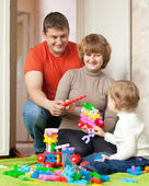Happy parents and child plays with meccano — Stock Photo