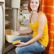 Stock Photo: Woman defrosting the refrigerator