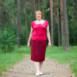 Mature woman walking in  forest — Stock Photo