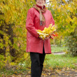 Mature woman in autumn park — Stock Photo #13671493