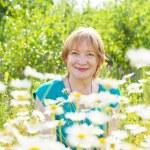 Mature woman camomile field — Stock Photo #13671500