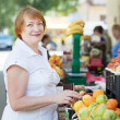 Foto Stock: Mature womchooses fruits