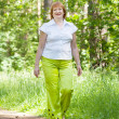 Walking mature womin forest — Stock Photo #13671540