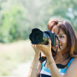 Female photographer takes photo — Stock Photo