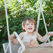 Laughing child on swing — Zdjęcie stockowe #13676044