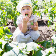 Baby girl eats cucumbers - Stock Photo