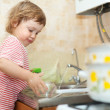 Royalty-Free Stock Photo: Baby girl  washes dishes