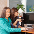 Two women using PC — Stockfoto