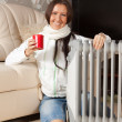 Woman with red cup near oil heater — Stockfoto