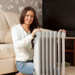 Woman  near warm radiator - 图库照片