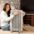 Foto Stock: Smiling womnear warm radiator